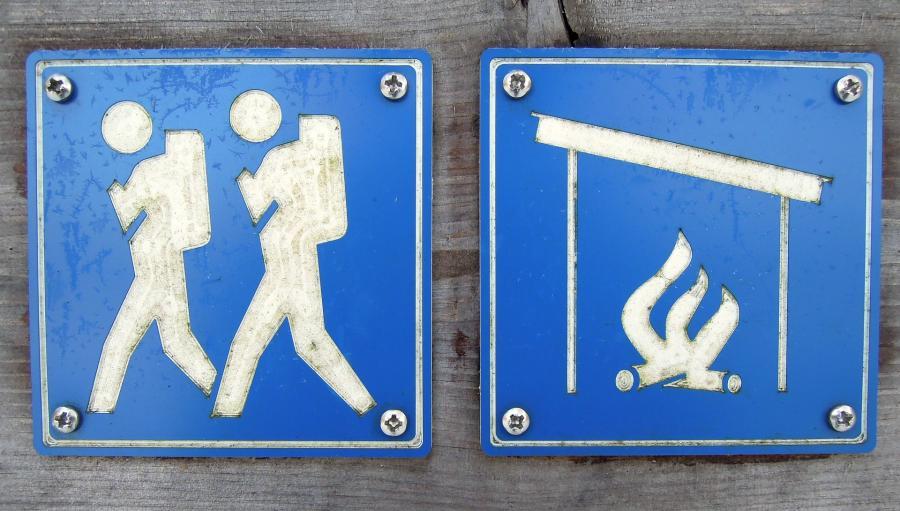 Skilt med vandrende mennesker og bålplads