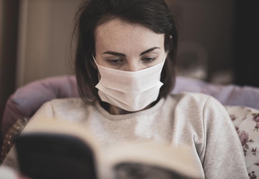 Kvinde med mundbind læser en bog