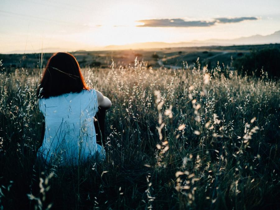 Person sidder i mark ved solnedgang