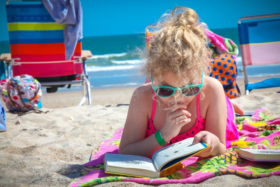 Pige ligger på stranden og læser