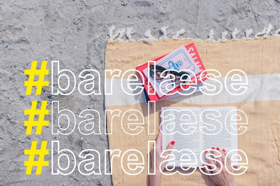 på en strand på et tæppe en stak bøger med solbriller ovenpå et par hænder der holder en bog